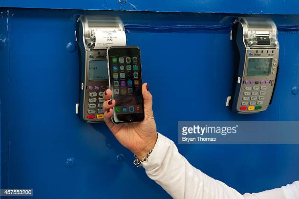 Ursula Anderman teaches New York pedestrians how to use Apple Pay as part of a Visa/Chase promotion on October 20 2014 in New York NY The software...