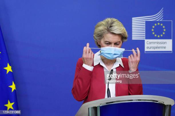 Ursula von der Leyen, president of the European Commission, removes her protective face mask during a Covid-19 vaccination target news conference in...