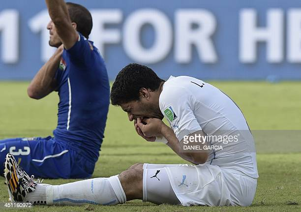 Uruguay forward Luis Suarez puts his hand to his mouth after clashing with Italy's defender Giorgio Chiellini during a Group D football match between...
