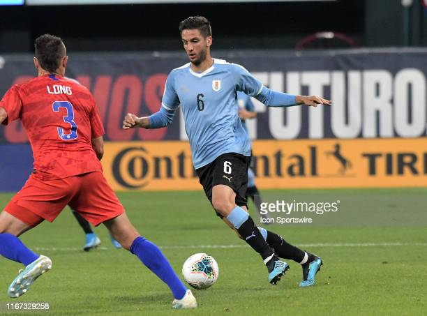 Uruguay midfielder Rodrigo Bentancur brings the ball up the field under pressure from USA defender Aaron Long during an exhibition soccer match...