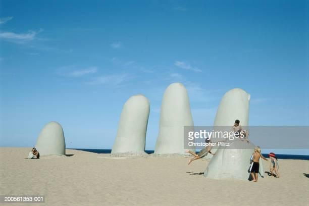 Uruguay, Punta del Este, children playing on sculpture on Brava beach