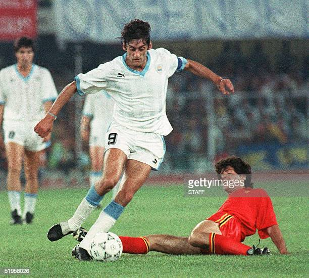 Uruguayan captain and midfielder Enzo Francescoli dribbles past the sliding tackle of Belgian midfielder Enzo Scifo during the World Cup first round...