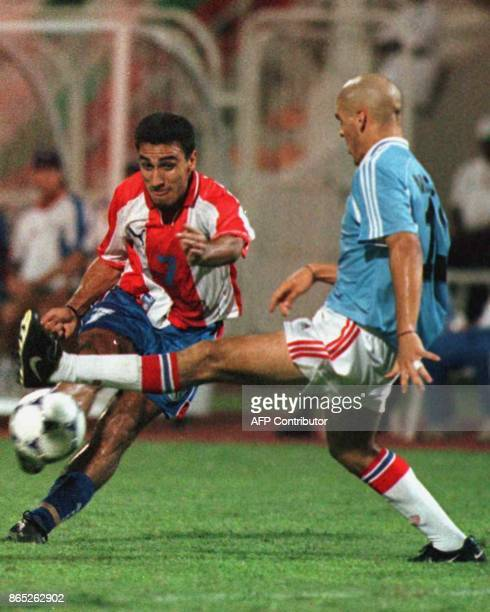 Uruguayan Damien Macaluso tries to stop from passing the ball Paraguayan Sergio Fernandez 14 April 1999 in Lagos for the quarter final of the under...