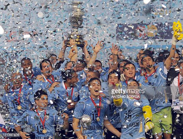 Uruguayan defender Diego Lugano raises the trophy and celebrates with teammates at the end of the 2011 Copa America football tournament final against...