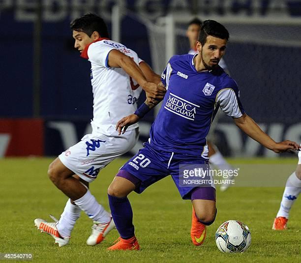 Uruguayan Defensor Sporting's Matias Cardacio vies for the ball with Paraguayan Nacional's player Silvio Torales during their Copa Libertadores...
