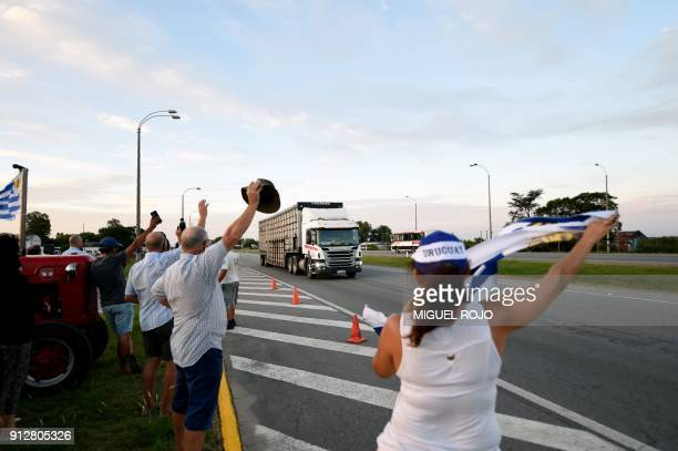 Uruguayan farmers wave to truck drivers as they hold a vigil on January 31 2018 outside the town of Progreso in Canelones department 35 km from...