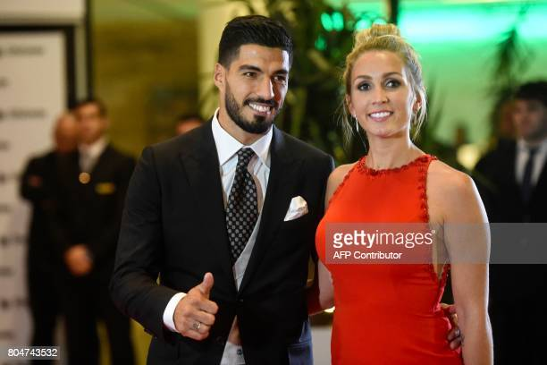 Uruguayan football player Luis Suarez and his wife Sofia Balbi pose on a red carpet during Barcelona's football star Lionel Messi and Antonella...
