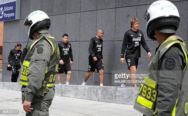 Uruguayan football players Jorge Rodriguez Diego Arismendi and Sebastian Fernandez walk next to Colombian policemen prior to a training session on...