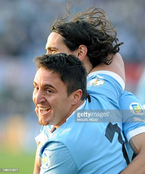 Uruguayan footballer Cristian Rodriguez celebrates with teammate Edinson Cavani after scoring the team's third goal against Peru during their Brazil...