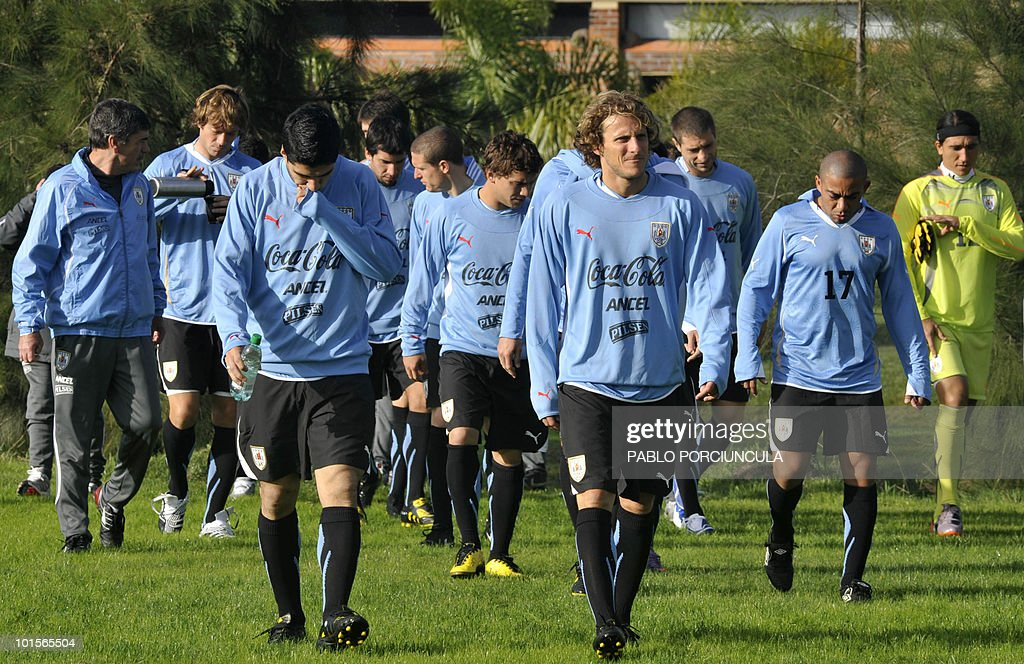 Uruguayan footballer Diego Forlan (C) walks with teammates for the official photo of the team on June 2, 2010 in Canelones, Uruguay. AFP PHOTO/Pablo PORCIUNCULA