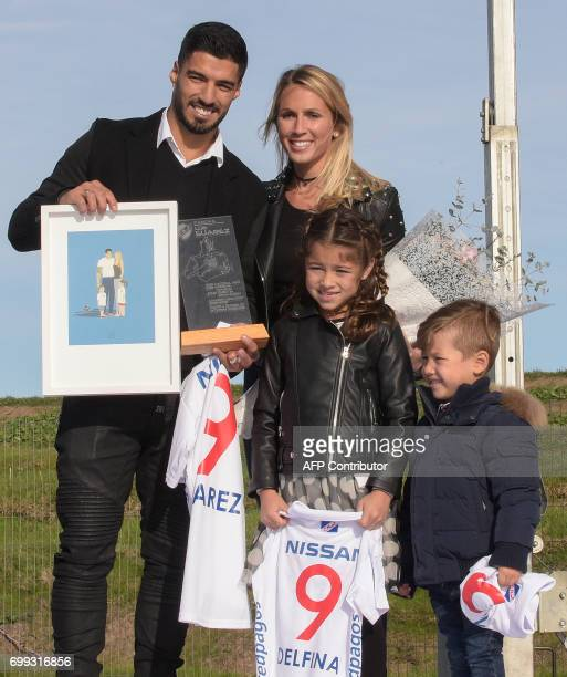 Uruguayan footballer Luis Suarez with his sons Benjamin and Delfina and wife Sofia pose during the inauguration of a football pitch with his name at...