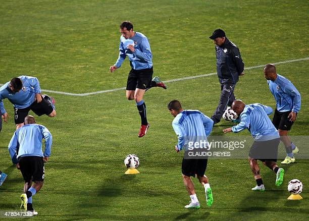 Uruguayan footballers warm up before the start of the 2015 Copa America football championship quarterfinal match Chile vs Uruguay in Santiago on June...