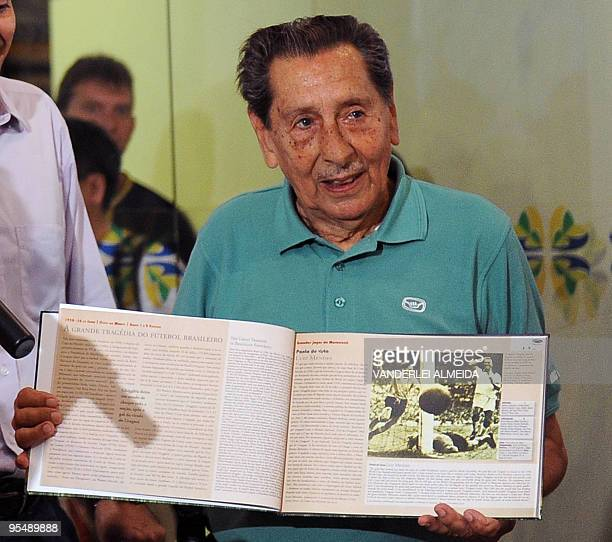 Uruguayan former footballer Alcides Ghiggia shows a book given as a gift by the Secretary of Tourism of Brazil Marcia Lins before leaving his...