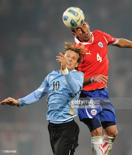 Uruguayan forward Diego Forlan and Chilean midfielder Mauricio Isla jump for the ball during the 2011 Copa America Group C first round football match...