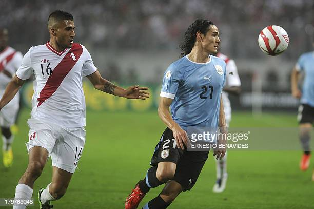 Uruguayan forward Edinson Cavani eyes the ball marked by Peruvian defender Josepmir Ballon during their FIFA World Cup Brazil 2014 qualifying...
