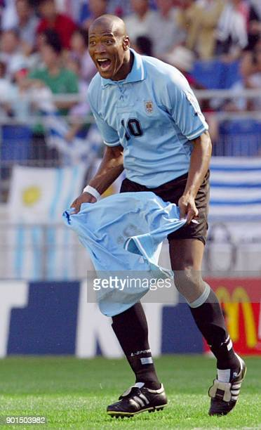 Uruguayan forward Richard Morales celebrates scoring his team's first goal against Senegal by pulling off his jersey to reveal teammate Fabian...