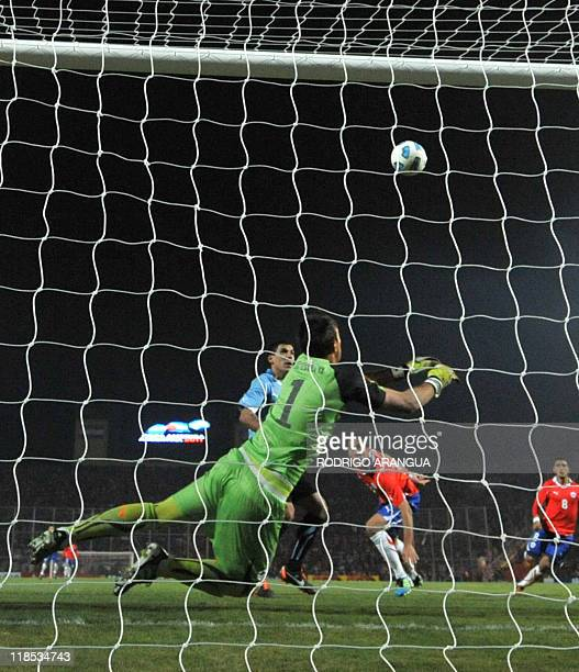 Uruguayan goalkeeper Fernando Muslera dives for the ball during a 2011 Copa America Group C first round football match against Chile held at the...