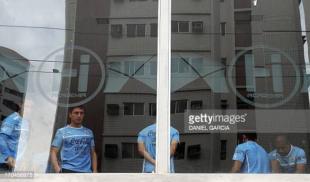 Uruguayan midfielder Cristian Rodriguez and teammates are seen beside a window during a training session at a gym in Recife Brazil on June 13 2013...