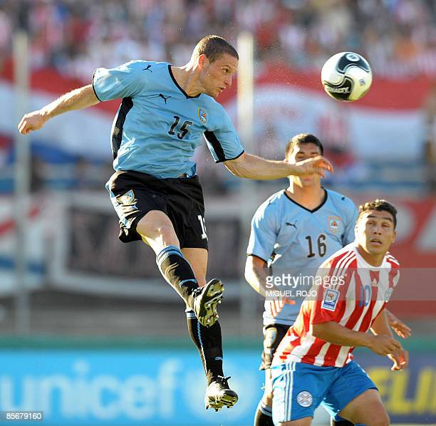 Uruguayan midfielder Diego Perez heads the ball next to Paraguayan forward Salvador Cabanas during their FIFA World Cup South Africa-2010 South...