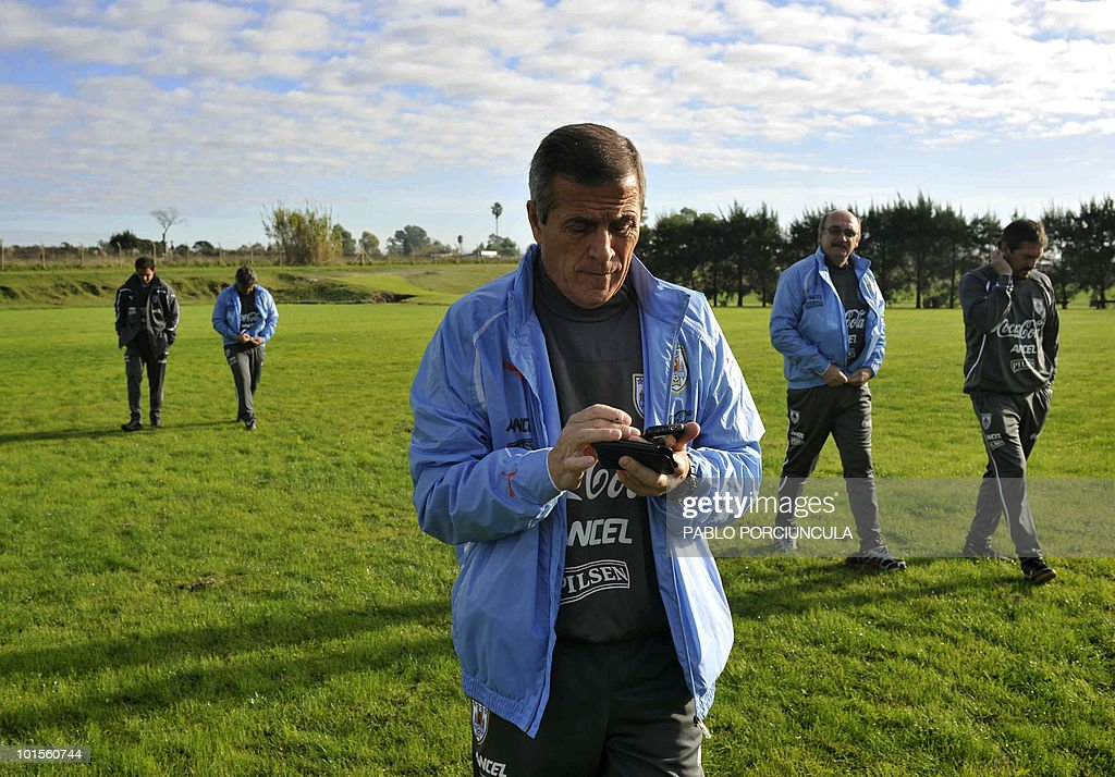 Uruguayan national football team coach Oscar Tabarez (C) checks his mobile phone before a training session on June 2, 2010 in Canelones, Uruguay. AFP PHOTO/Pablo PORCIUNCULA