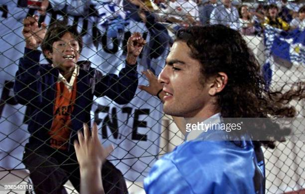 Uruguayan player Federico Magallanes celebrates with a young fan 13 July after their match against Chile in Asuncion Uruguay won the match 64 on...