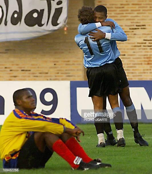 Uruguayan player Gabriel Alvez hugs teammate Marcelo Zalayeta after scoring the first goal for Uruguay as Ecuadoran player Ivan Hurtado sits on the...