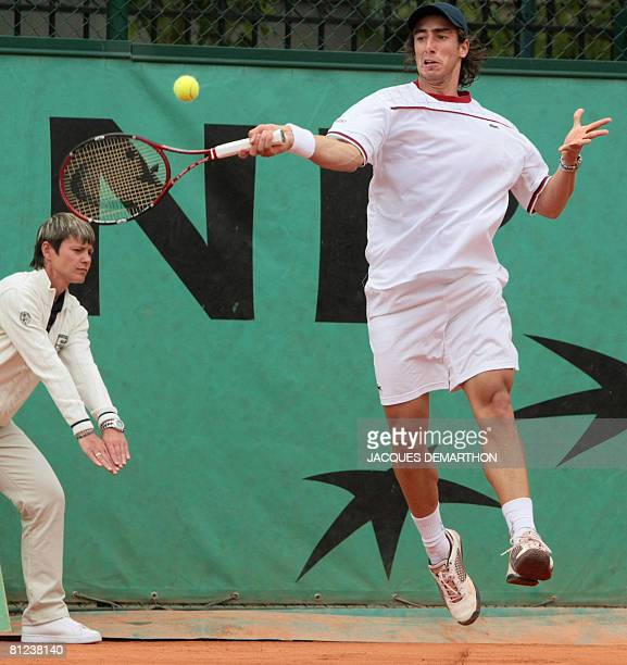 Uruguayan player Pablo Cuevas hits a return to his Chilean player Fernando Gonzalez during their French tennis Open first round match at Roland...