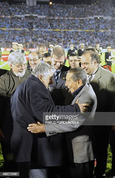 Uruguayan President Jose Mujica embraces former 1950 WC champion Uruguayan Alcides Ghiggia before the farewell football match between Uruguay and...