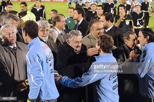 Uruguayan President Jose Mujica his VicePresident Danilo Astori and former 1950 World Cup champion Alcides Ghiggia shake hands with Uruguayan...