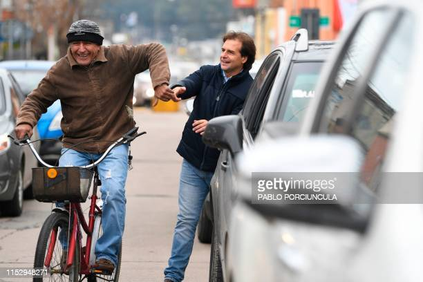 Uruguayan presidential precandidate of the National Party Luis Lacalle Pou is greeted by a supporter riding a bicycle as he arrives to vote a polling...