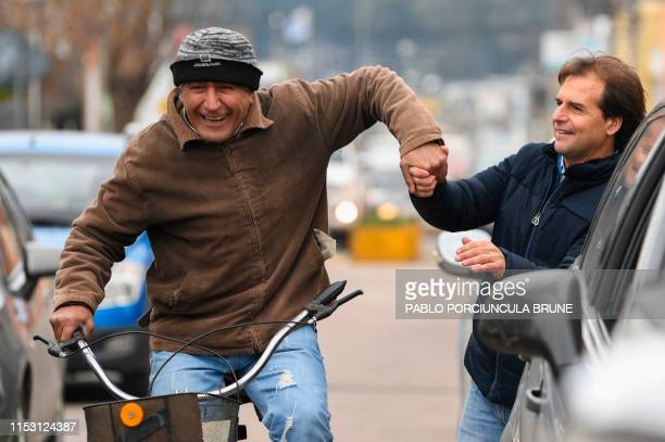Uruguayan presidential precandidate of the National Party Luis Lacalle Pou is greeted by a supporter riding a bicycle as he arrives at the polling...
