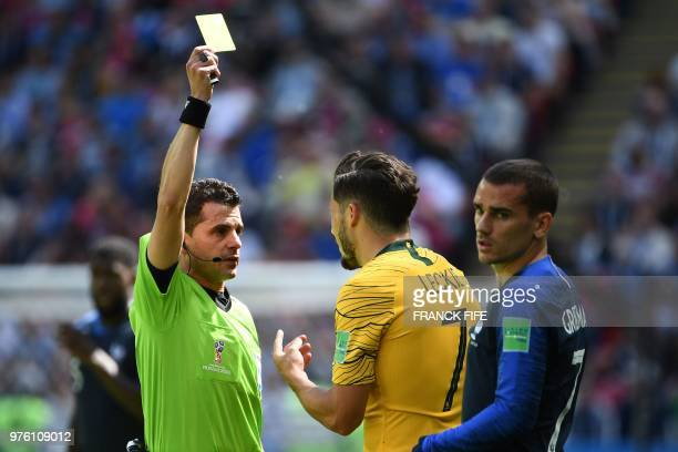Uruguayan referee Andres Cunha shows a yellow card to Australia's forward Mathew Leckie beside France's forward Antoine Griezmann during the Russia...