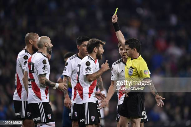 TOPSHOT Uruguayan referee Andres Cunha shows the yellow card to River Plate's Leonardo Ponzio during the second leg match of the allArgentine Copa...