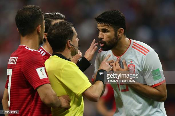 Uruguayan referee Andres Cunha speaks to Spain's forward Diego Costa during the Russia 2018 World Cup Group B football match between Iran and Spain...