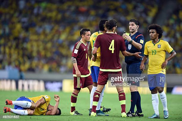 Uruguayan referee Dario Ubriaco shows the yellow card to Venezuela's Oswaldo Vizcarrondo for fouling Brazil's Ricardo Oliveira during the Russia 2018...