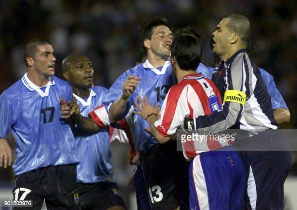 Uruguayan soccer players Walter Pandiani and Marcelo Zalayeta and Fabian O'Neil shout at Paraguayan goalkeeper Jose Chilavert during incidents that...