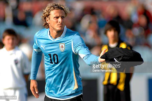 Uruguayan striker Diego Forlan receives the FIFA Golden Ball from players Alcides Ghiggia and Pablo Forlan on June 08 2011 in Montevideo Uruguay
