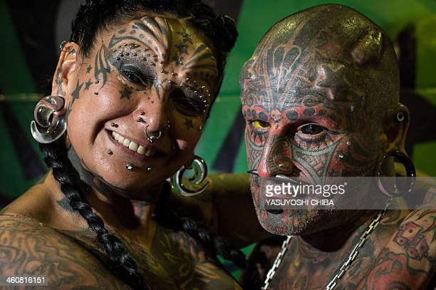 Uruguayan tatoo artist Victor Hugo Peralta and his wife Argentinian tatoo artist Gabriela Peralta pose for a picture during the Tatoo Week Rio in Rio...