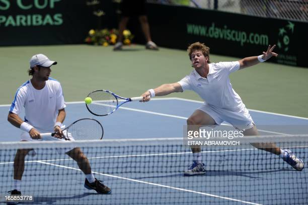 Uruguayan tennis player Ariel Behar reaches for the ball as partner Marcel Felder looks on during their Davis Cup Americas Group I second round...