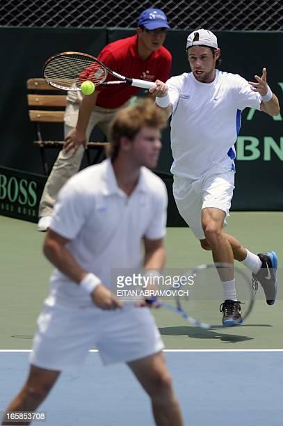 Uruguayan tennis player Marcel Felder returns the ball as partner Ariel Behar looks on during their Davis Cup Americas Group I second round doubles...