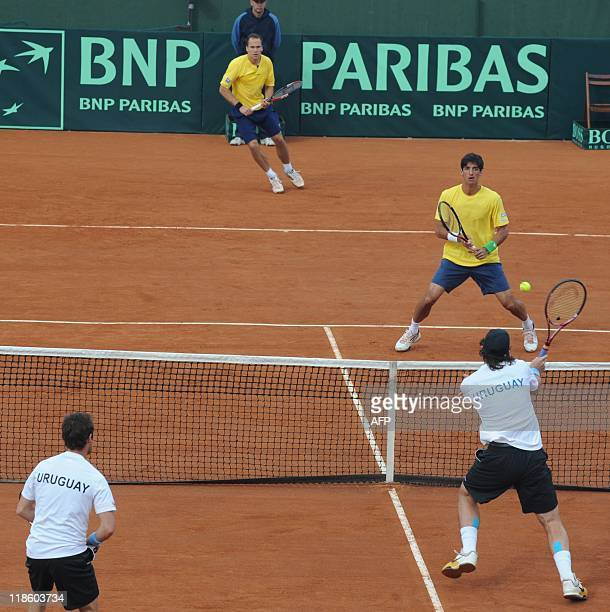 Uruguayan tennis player Martin Cuevas returns the ball next to teammate Marcel Felder facing Brazilians Thomas Bellucci and Bruno Soares during their...