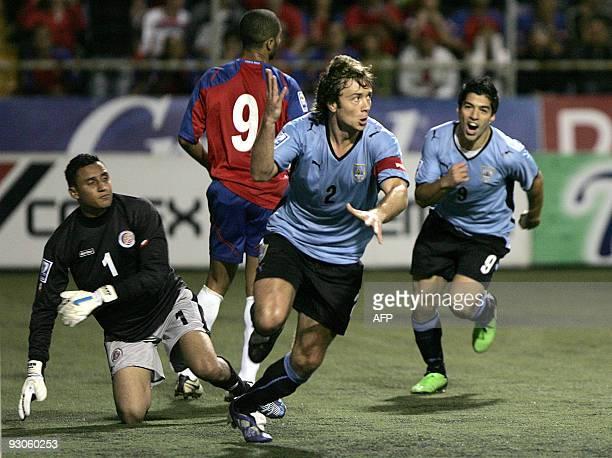 Uruguayan's Diego Lugano celebrates with teammate Luis Suarez next to Costa Rica´s Alvario Saborio and goalkeeper Keilor Navas after scoring against...