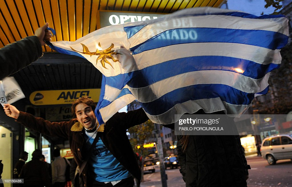Uruguayans football fans celebrate at the end of the 2010 World Cup group A first round football match Uruguay vs South Africa along 18 de Julio main avenue in downtown Montevideo, June 16, 2020. Uruguay won 3-0. AFP PHOTO/Pablo PORCIUNCULA