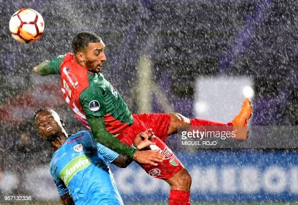 TOPSHOT Uruguay's Boston River midfielder Wiston Fernandez jumps for a header with Colombia's Jaguares midfielder Deinner Quinonez during their 2018...