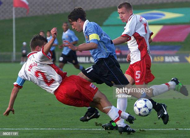 Uruguay's Captain Horacio Peralta looses posession as he trips over the Poland defence of Marcin Rogalski and Wojciech Szymanek during their match in...