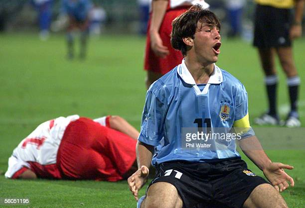 Uruguay's captain Horacio Peralta shows his frustration at the outcome of his tackle with Poland's Sebastian Mila who also lies on the ground during...