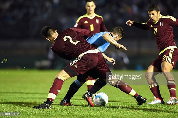 Uruguay's Cristian Rodriguez is marked by Venezuela's defenders Wilker Angel and Alexander Gonzalez during their Russia 2018 World Cup football...