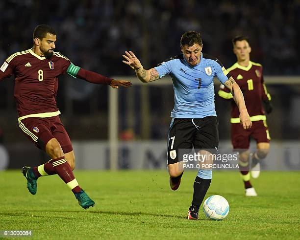 Uruguay's Cristian Rodriguez is marked by Venezuela's midfielder Tomas Rincon during their Russia 2018 World Cup football qualifier match in...