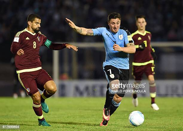Uruguay's Cristian Rodriguez vies for the ball with Venezuela's midfielder Tomas Rincon during their Russia 2018 World Cup qualifier football match...
