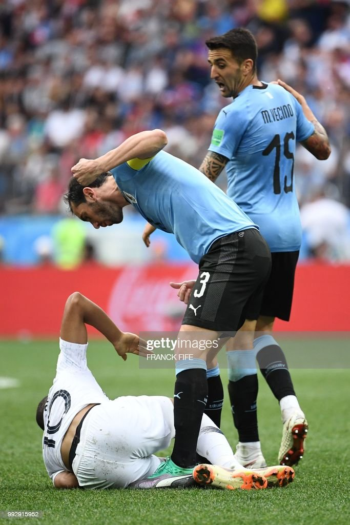 Uruguay's defender Diego Godin (C) gestures as France's forward Kylian Mbappe lies on the ground during the Russia 2018 World Cup quarter-final football match between Uruguay and France at the Nizhny Novgorod Stadium in Nizhny Novgorod on July 6, 2018. (Photo by FRANCK FIFE / AFP) / RESTRICTED